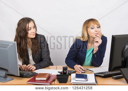Office Worker Looking With Distaste At The Colleague Sitting Next To Staring At A Computer Monitor