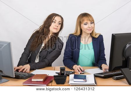 Office Worker On The Sly Looks At The Monitor Colleague Sitting Next To A Computer