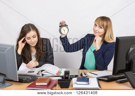 In The Office, One Employee Is Looking Forward To The End Of The Day, While The Other Continues To W