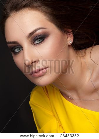 Portrait of beautiful woman with evening make-up in yellow dress