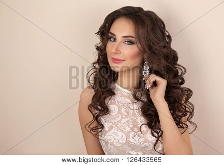 Portrait of beautiful woman with makeup and evening hairstyle in white dress