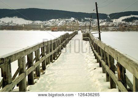 Old abandoned bridge over the river in the winter.