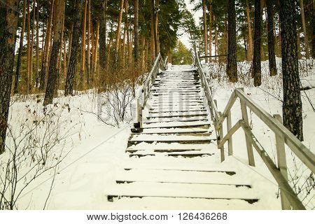 Old abandoned wooden staircase with a broken railing covered with snow.