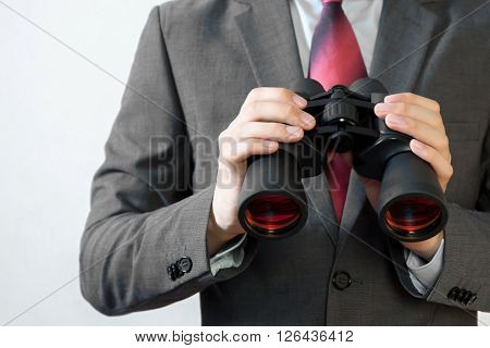 Businessman Looking For Something With Binoculars Such As Business Opportunities / Jobs / New Market