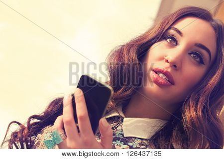 Young good-looking urban girl using cellphone outdoors.