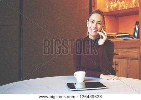 Young business woman with beautiful smile talking on mobile phone with friend while sitting in coffee shop interiorcheerful happy female is having cell telephone conversation.Copy space area for text