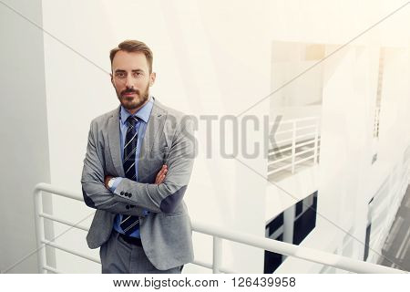 Young man professional banker dressed in luxury suit is standing with crossed arms in modern office interior near copy space. Male intelligent CEO is waiting business partners in hallway his company