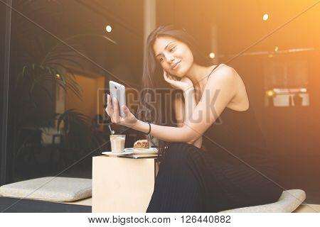 Young latin woman making self portrait on her smartphone digital camera while sitting in sidewalk cafe during lunch break. Pretty female posing while photographing herself for social network picture