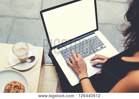 Back view of business woman is typing text on laptop keyboard during work break in cafe. Female freelancer is working on net-book with mock up blank copy space screen for your text message or concept