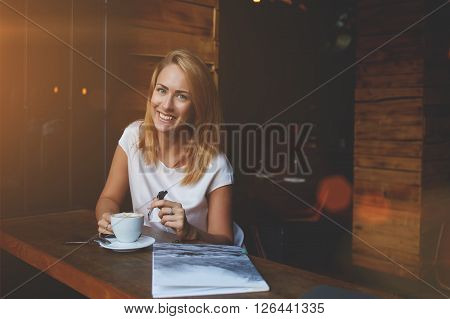 Attractive happy hipster girl with good mood posing while sitting alone in modern coffee shop interior cheerful Caucasian woman with beautiful smile enjoying her recreation time in cozy cafe bar poster