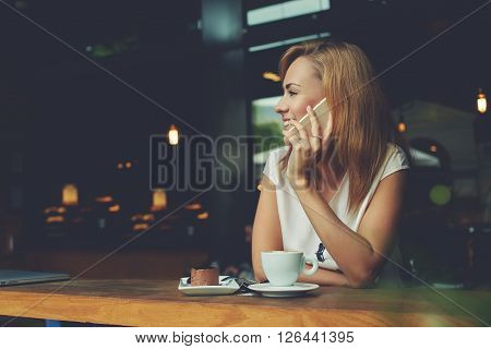 Young happy hipster girl speaking with her friend by mobile phone while relaxing in cozy coffee shop charming lady with beautiful smile talking on cell telephone while sitting in cafe during lunch