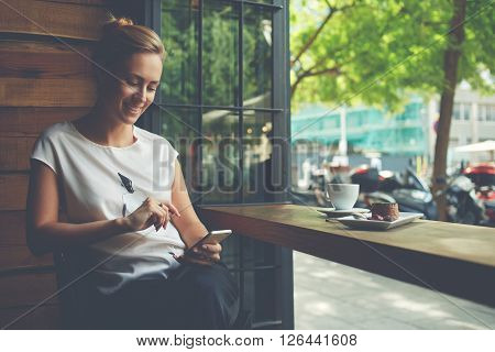Charming woman with beautiful smile reading good news on mobile phone during rest in coffee shop happy Caucasian female watching her photos on cell telephone while relaxing in cafe during free time