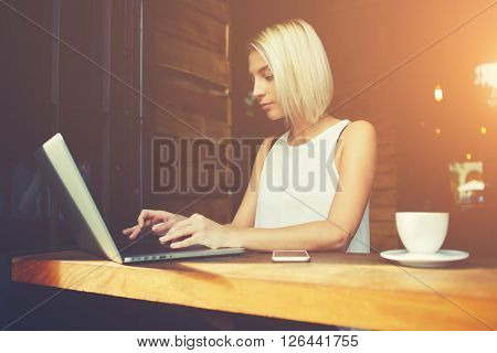 Young attractive lady keyboarding something on portable net-book while sitting in coffee shop during work break beautiful smart female student using laptop computer to prepare for the coursework