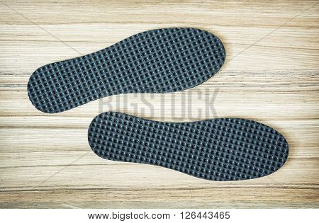 New orthopedic shoe insoles on the wooden background.