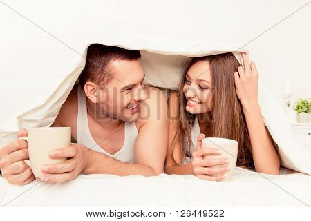 Cheerful Man And Woman Basking With Blanket And Hot Tea