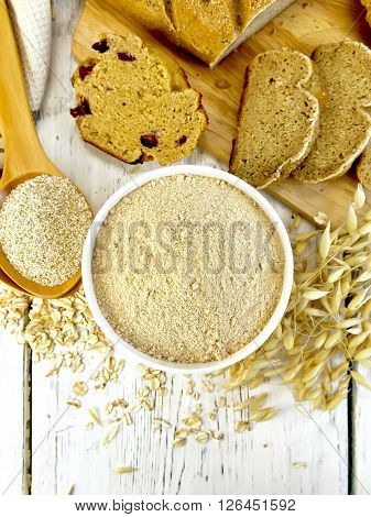 Oat flour in white bowl, oat bran in spoon, oatmeal and stems, bread and biscuits on a background of wooden boards on top