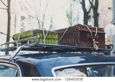 Vintage suitcases on a car roof. Travel with old vintage suitcase tied with a rope to car roof rack.  Retro travel, trip, journey to vacation. Old retro auto. Vintage suitcase. Summer travel.