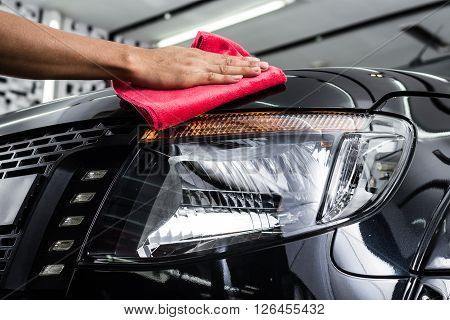 Car detailing series : Worker cleaning black car