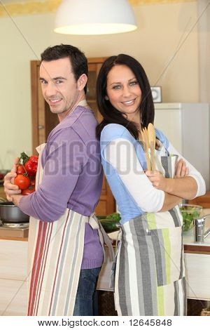 Couple standing back to back in the kitchen