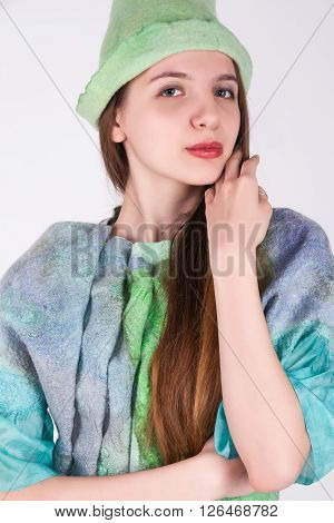 the young beautiful charming girl in a turquoise suit in modernist style poses in a camera