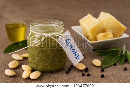 Pesto with almonds and pecorino cheese in a glass jar on a wooden table ** Note: Visible grain at 100%, best at smaller sizes