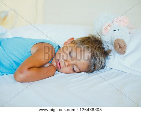 Cute little boy sleeping with lovely toys