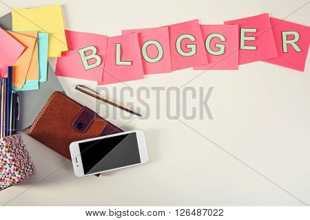Blogger word on a table with  phone and pocketbook.