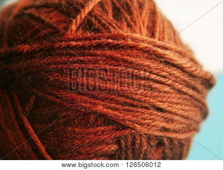 A brown, tightly spun ball of yarn