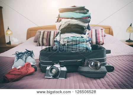Luggage with pile of clothes, camera, sunglasses and other items on bed