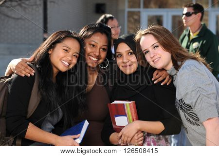 Group of diverse students in a group with others in the background