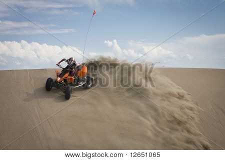 Teen riding ATV quadbike in desert