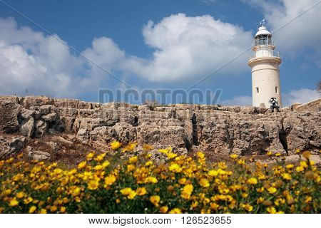 PAPHOS, CYPRUS - MARCH 16, 2016: Tourist under the lighthouse at Paphos point peninsula. The lighthouse was built in 1888, and its light can be seen for 17 nautical miles
