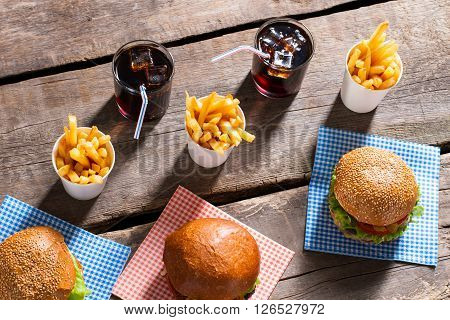Hamburgers with fries and cola. Drinks and burgers on table. Energy for the whole day. Freshness and satiety.