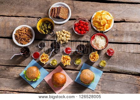 Burgers with fries and chips. Lots of food on table. Fresh food at local bistro. Junk food and vegetables.