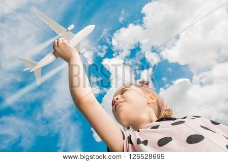 Airplane Flight Dream. Beautiful Six Year Old Caucasian Girl Playing with Airplane Model Simulating Aircraft in Flight.