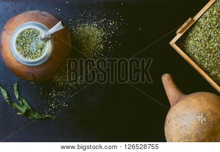 Yerba mate in calabash and dry herb in clay bowl on black background. Top view