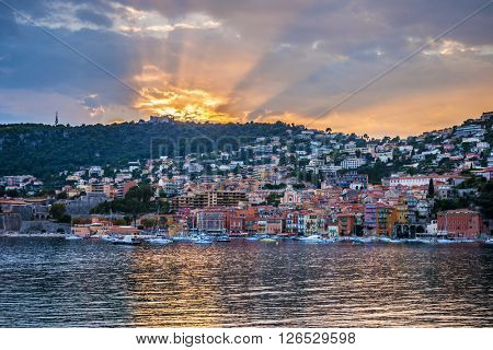 Coast view of colourful French Riviera town Villefranche-sur-Mer at dramatic sunset with sunrays reflecting in harbour.