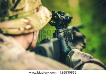 Wildlife Hunting. Camouflaged Hunter with Powerful Rifle with Scope Spotting Animals.