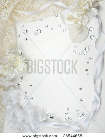 Border of ivory and white colored lace and ribbons with silk flowers and shiny baubles good for weddings and anniversaries with copy space