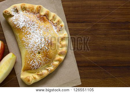 Chilean apple empanada with icing sugar photographed overhead on dark wood with natural light