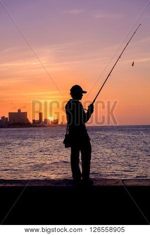 Beautiful sunset in Havana with the silhouette of a fisherman on the Malecon seawall