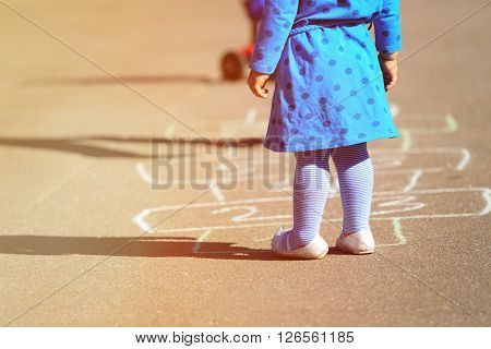 little girl playing hopscotch on playground, kids outdoor activities
