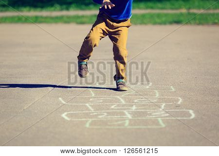 little boy playing hopscotch on playground, kids outdoor activities