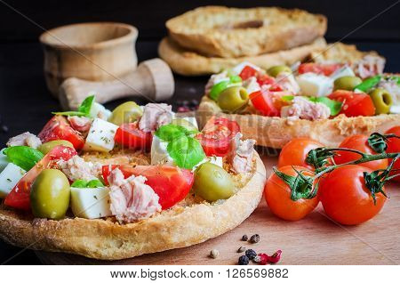Classical frisella tomato, cheese mozzarella, tuna and olives. Italian starter friselle. Dried bread called freselle on wooden board with tomatoes cherry. Italian food. Healthy vegetarian food.