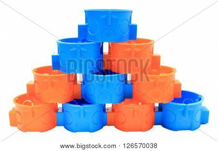 Stack of blue and orange plastic electrical boxes on white background junction boxes accessories for engineering jobs