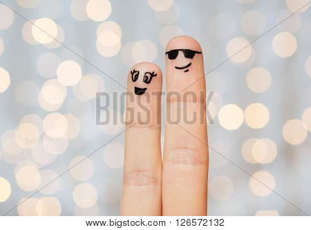 family, couple, people and body parts concept - close up of two fingers with smiley faces over holidays lights background