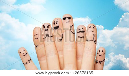 gesture, family, people and body parts concept - close up of two hands showing fingers with smiley faces over blue sky and clouds background