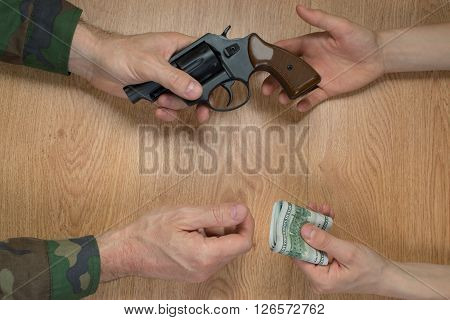 Transfers of money in exchange for a gun under certain conditions, sitting at the table.