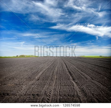 Beautiful spring landscape with plowed field under blue sky with clouds,