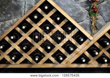Resting wine bottles stacked on wooden racks in cellar